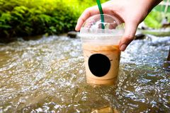 Cup of coffee with flowing water in stream Stock Photos