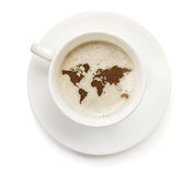 Cup of coffee with foam and powder in the shape of World.(series Royalty Free Stock Photography