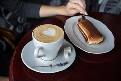 Cup of coffee with foam and tiramisu cake. A cup of coffee with foam and a tiramisu cake on the table Royalty Free Stock Images