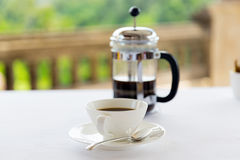 Cup of coffee and french press on table Stock Photos