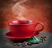 Cup of coffee. Cup of fresh coffee with coffee beans on wooden table Royalty Free Stock Image