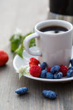 Cup of coffee and fresh berries on a wooden table.  royalty free stock images
