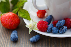 Cup of coffee and fresh berries on a wooden table.  royalty free stock photo