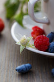 Cup of coffee and fresh berries on a wooden table.  royalty free stock photography