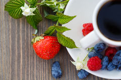 Cup of coffee and fresh berries on a wooden table.  stock photos