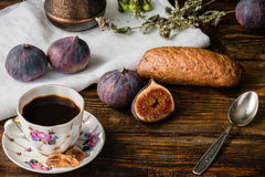 Cup of coffee with fresh bun and some figs. On wooden table Stock Images