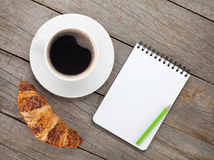 Cup of coffee, fresh croissant and notepad Stock Photos