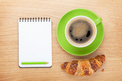 Cup of coffee, fresh croissant and notepad Royalty Free Stock Photography