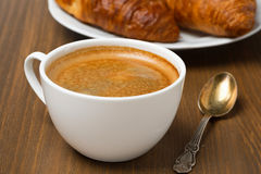 Cup of coffee and fresh croissants, selective focus Royalty Free Stock Photos