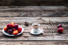 Cup of coffee and fresh plums on wood, free space Stock Image
