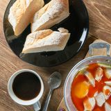A cup of coffee with fresh sliced Italian bread and panned egg a. Nd sausage Royalty Free Stock Images