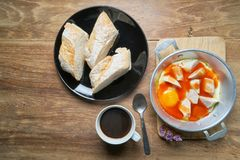 A cup of coffee with fresh sliced Italian bread and panned egg a. Nd sausage Stock Photography