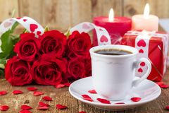Cup with coffee in front of bouquet of red roses Royalty Free Stock Photography