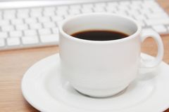 Cup of coffee in front of keyboard Royalty Free Stock Images
