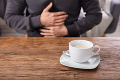 Cup Of Coffee In Front Of Man Having Stomach Pain. Man Suffering From Stomach Pain With Cup Of Coffee On Wooden Desk stock images