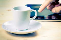 Cup of coffee in front of the tablet, concept of new technology Royalty Free Stock Images