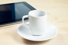Cup of coffee in front of the tablet, concept of new technology Royalty Free Stock Photography