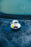 Cup of coffee on a frozen blue car. Hot strong Cup of coffee with chocolate on the frozen hood of the blue car. Morning, cold, frost, hoarfrost, waiting Stock Photo