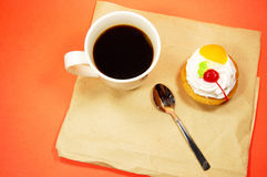 Cup of coffee and fruit cake on a paper Royalty Free Stock Images