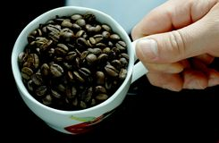 Cup of coffee full with beans. Cup of coffee full with coffe beans royalty free stock photography