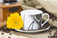 Cup of coffee with gerbera and coffee beans Royalty Free Stock Photo