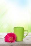 Cup of coffee and gerbera on wooden table Stock Image