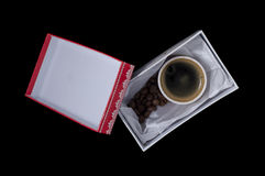 A cup of coffee in a gift box. On a black background Royalty Free Stock Images