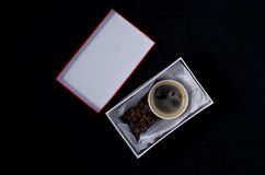 A cup of coffee in a gift box. On a black background Royalty Free Stock Photography