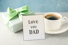 Cup of coffee, gift box with green ribbon and inscription Love you DAD on white table against blue background stock images