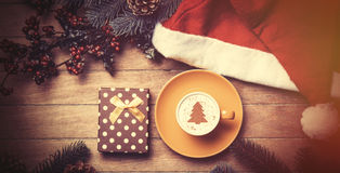 Cup of coffee and gift box with pine and hat on table. royalty free stock images