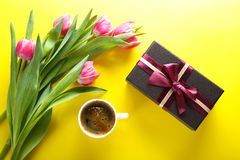 Cup of coffee, gift box and pink tulips on yellow background, to Stock Photography
