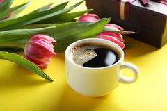 Cup of coffee with gift box and tulips bouquet on yellow backgro Royalty Free Stock Photo