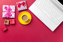 Cup of coffee and gift near computer Stock Images