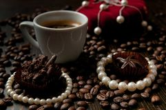 Cup of coffee with a gift necklace and coffee beans in background and a red luxury box with jewlery. Cup of coffee with a gift necklace and coffee beans in royalty free stock images