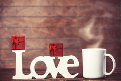 Cup of coffee, gift and word Love Stock Photos