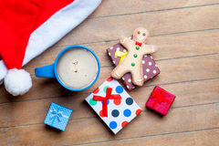 Cup of coffee, gifts, gingerbread man and santa claus hat on the Royalty Free Stock Photo