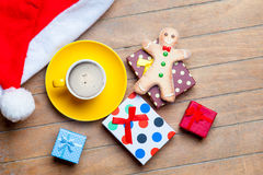 Cup of coffee, gifts, gingerbread man and santa claus hat on the Royalty Free Stock Photography