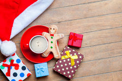 Cup of coffee, gifts, gingerbread man and santa claus hat on the Stock Photo