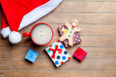 Cup of coffee, gifts, gingerbread man and santa claus hat on the Stock Photos