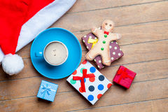 Cup of coffee, gifts, gingerbread man and santa claus hat on the Stock Images