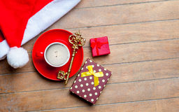 Cup of coffee, gifts, golden key and santa claus hat on the wond Royalty Free Stock Photo