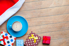 Cup of coffee, gifts and santa claus hat on the wonderful brown Royalty Free Stock Photography