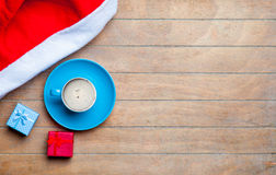 Cup of coffee, gifts and santa claus hat on the wonderful brown Stock Image