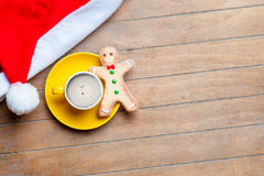 Cup of coffee, gingerbread man and santa claus hat on the wonder Royalty Free Stock Images