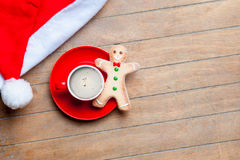 Cup of coffee, gingerbread man and santa claus hat on the wonder Stock Photo