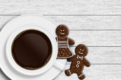 Cup of coffee, gingerbread man and woman lying on wooden desk Stock Photo