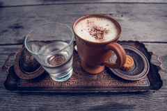 Cup of coffee, a glass of water and cookies on the wooden table. A ceramic cup of coffee, a glass of pure water and cookies on the wooden table in austrian Stock Photo