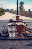 Cup of coffee, a glass of water and cookies on the wooden table. Stock Images