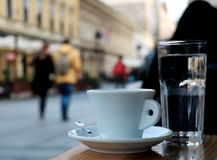 Cup of coffee and a glass of water. Cup of coffee on the table next to the promenade Royalty Free Stock Photography