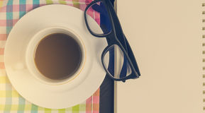 Cup of coffee with glasses and book page. Stock Images